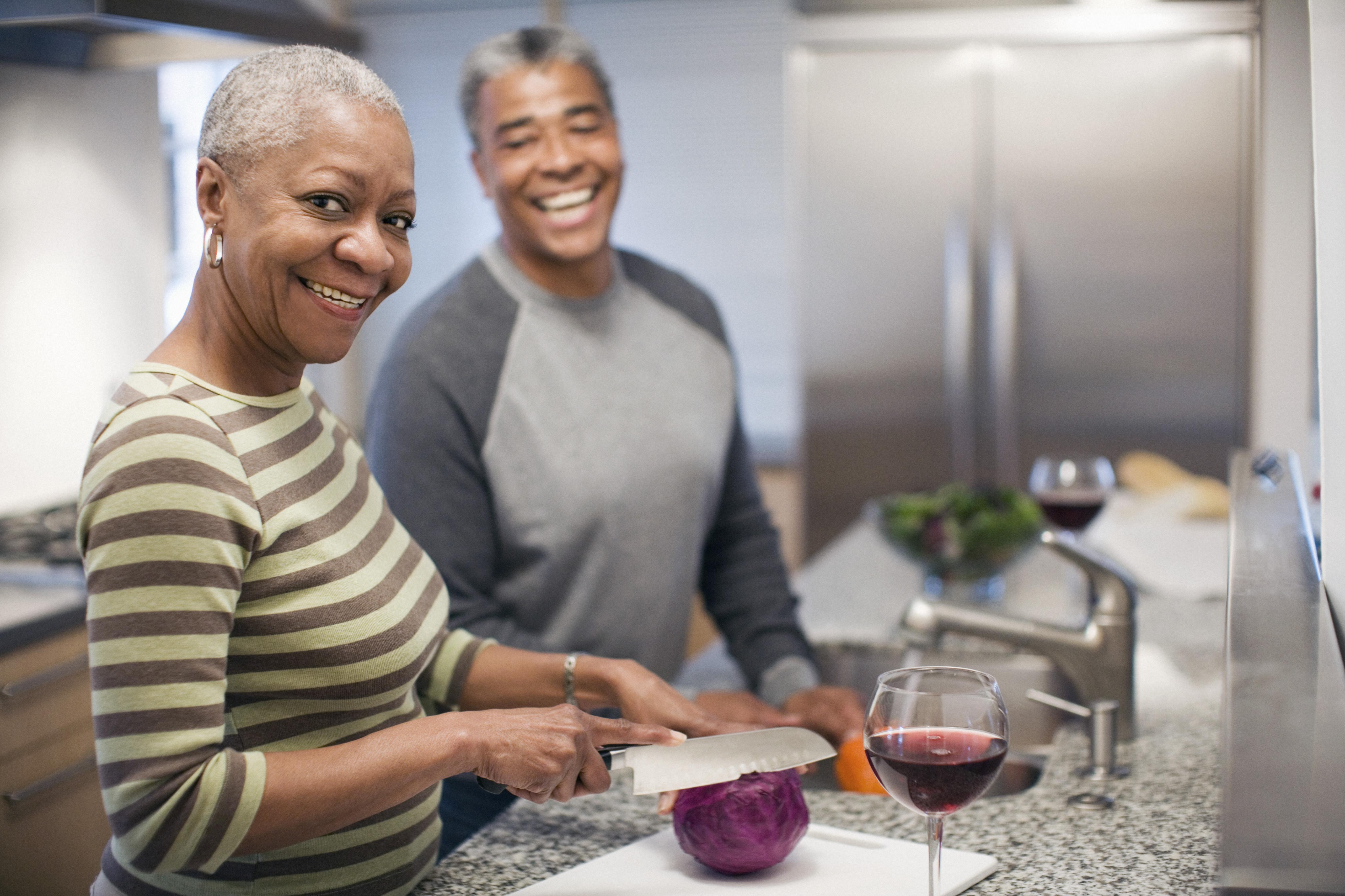Laughing couple preparing dinner