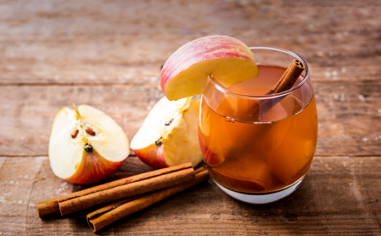 Hot apple cider with cinnamon stick on wooden background, healthy lifestyle